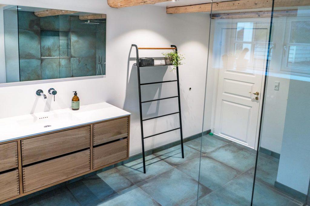 Moderne fliser og synlige træbjælker på badeværelse